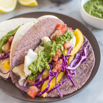 Delicious fish tacos with a spicy and tangy green harissa. Add some spice to your dinner or lunch with these healthy tacos! | healthynibblesandbits.com