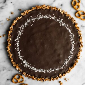 Five-Ingredient Chocolate Coconut Tart with Pretzel Crust - this rich gluten-free dessert is a must make for your next gathering! by Lisa Lin of Healthy Nibbles & Bits