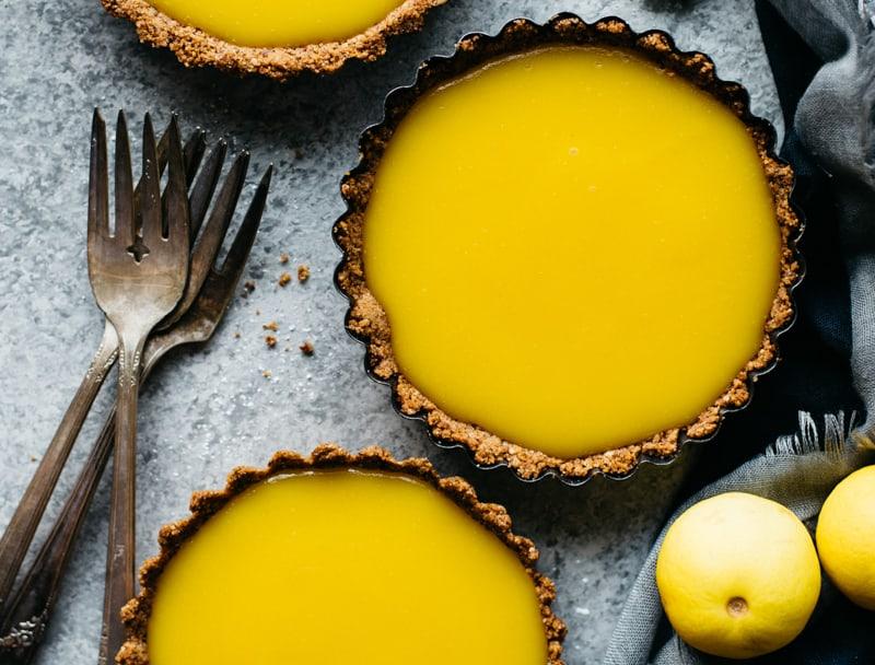 Gluten-Free Lemon Tarts - sharp lemon curd is paired with a gluten-free nut flour and graham cracker crust.