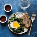 Green Shakshuka - a healthy breakfast dish filled with kale, collard greens and sunny side up eggs. An easy gluten-free meal!