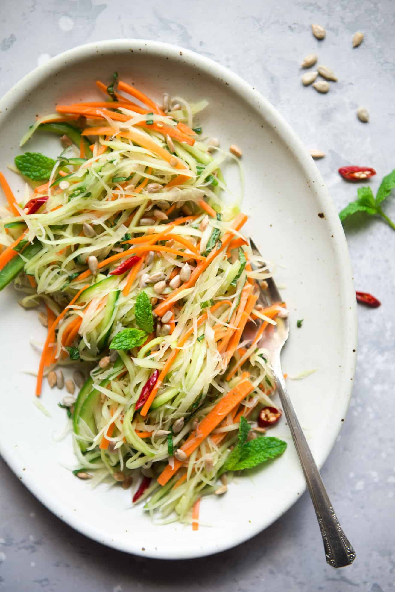 Green Papaya Salad - This vegan green papaya salad is a delicious light salad that is great as an appetizer. It is dressed with a light, tangy dressing made of rice vinegar, garlic, shallots and maple syrup.