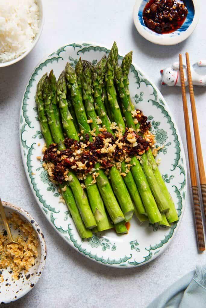 Una foto de espárragos asados con guindilla y ajo junto con una guarnición de arroz, palillos, ajo frito y chiles crujientes de Lao Gan Ma.