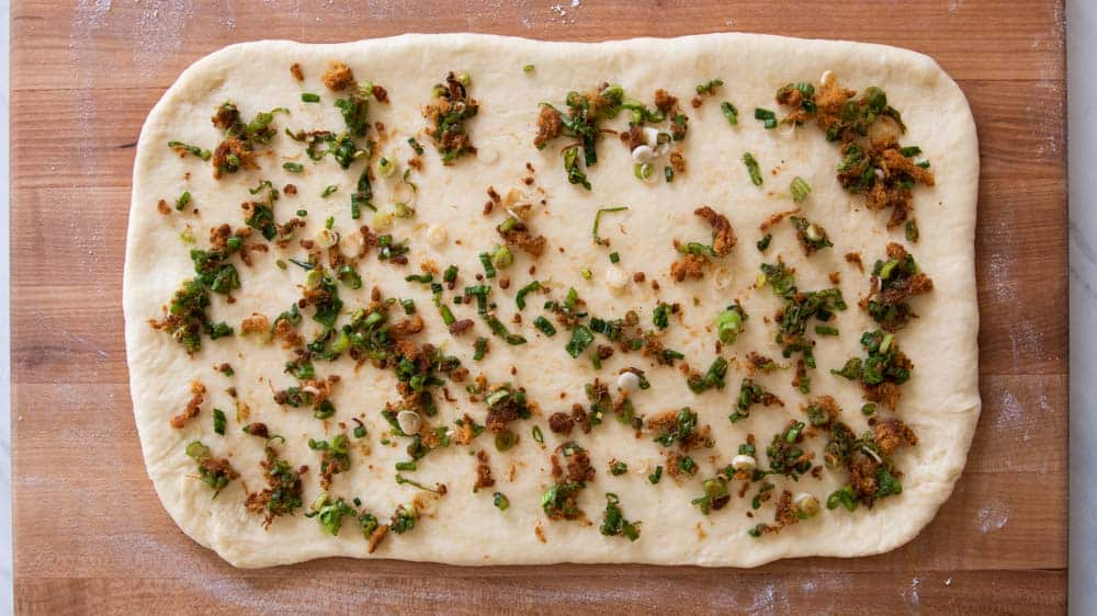 Dough rolled out the first time and topped with scallion and pork floss filling